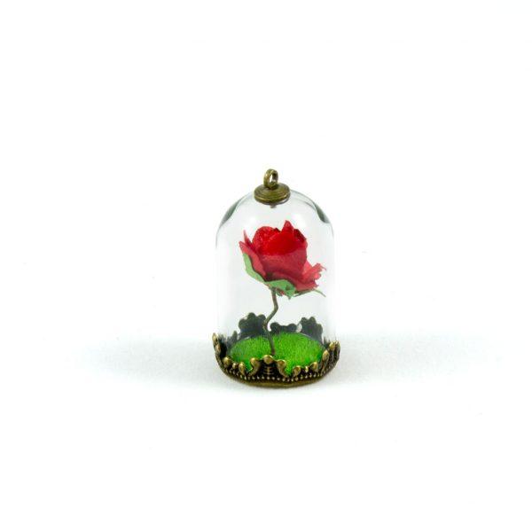 Detalle de colgante que incluye una rosa en miniatura y una base de césped artificial
